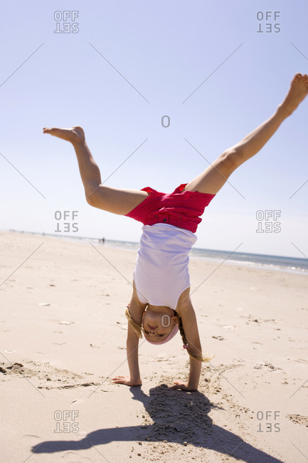 Germany, Baltic sea, Girl (6-7) doing handstand on beach