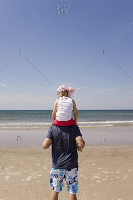 Germany, Baltic sea, Father carrying daughter (6) on shoulders, rear view