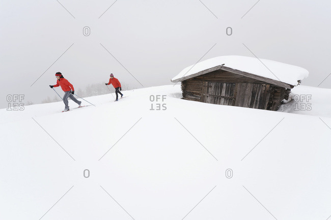Italy, South Tyrol, Couple cross-country skiing, next to cabin