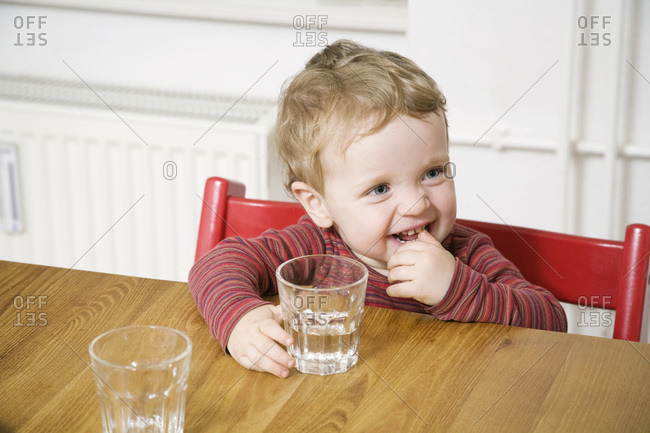 Germany, Berlin, Boy (2-3) sitting at table, holding glass of water