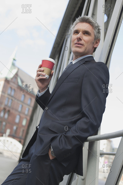 Germany, Hamburg, Businessman leaning on railing, holding mug of coffee