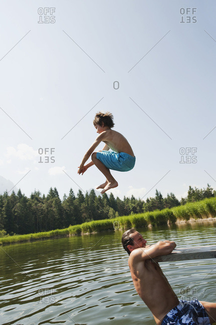 Italy, South Tyrol, Father and son (10-11), son jumping into lake