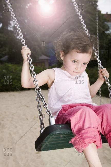 Germany, Berlin, Girl (3-4) on swing, portrait