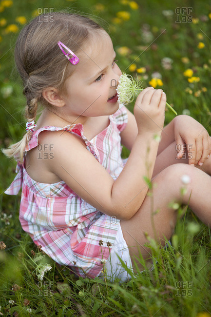 Germany, Bavaria, Girl (4-5) smelling flower, side view