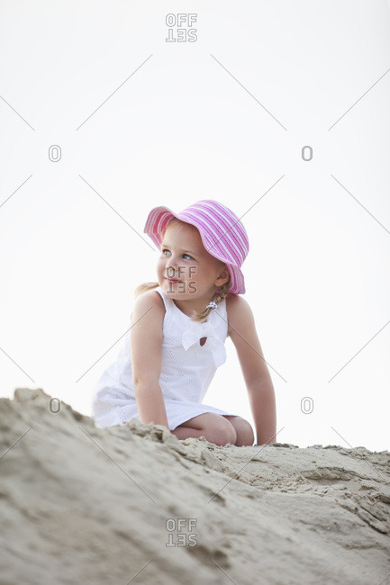 Germany, Girl (4-5) kneeling on sand dune, looking away, portrait