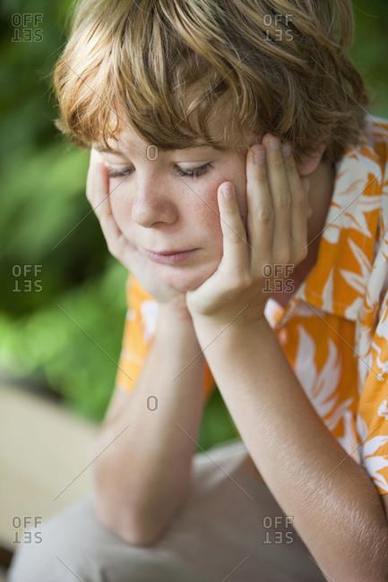 Germany, Bavaria, Teenage boy (13-14) head in hands, looking down, portrait, close-up