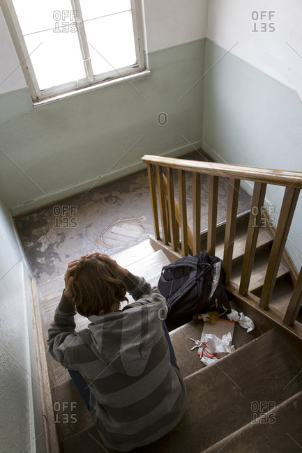 Germany, boy  sitting on stairs, hands on head, rear view