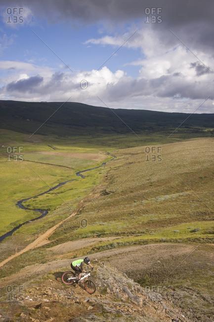 Iceland, Man mountain biking across hilly landscape