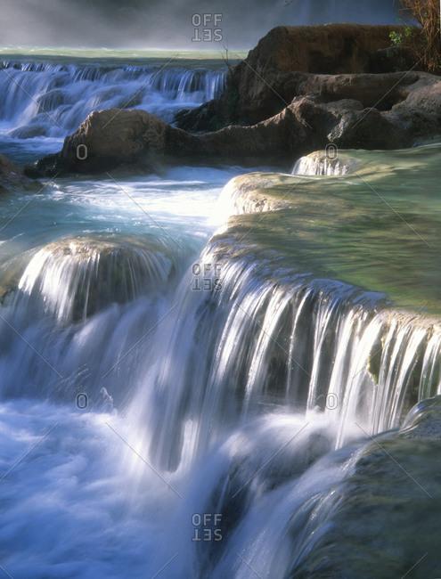 Water flowes over travertine formations below Havasu Falls.