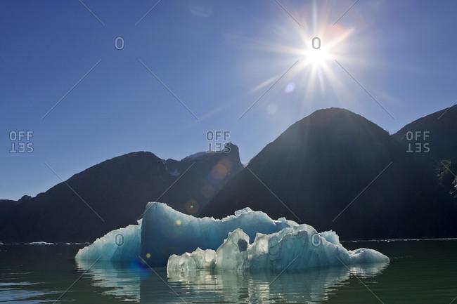 Sunburst and blue iceberg with mountains on the skyline.