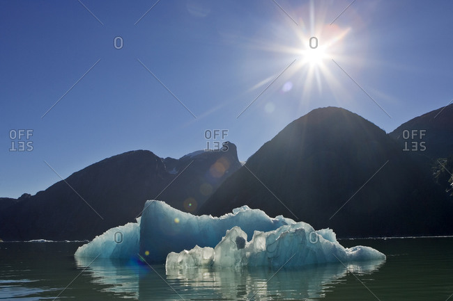 Sunburst and blue iceberg with mountains on the skyline.