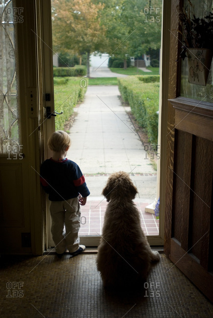 A little boy looks out his front door in Nebraska.