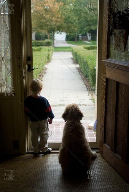 A little boy looks out his front door in Nebraska.