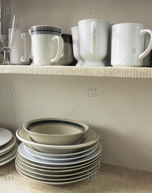 Close up of mugs and plates on shelf