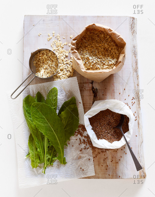 Oat, flax seeds and chicory leaves on wooden cutting board