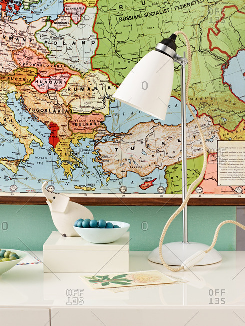 Table lamp on table with map behind