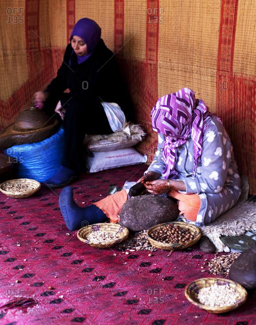 Two women crushing nuts