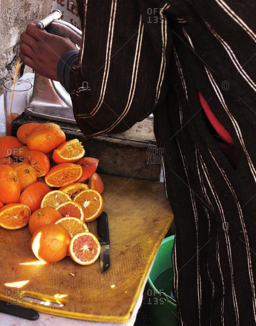 Close up of man squeezing oranges