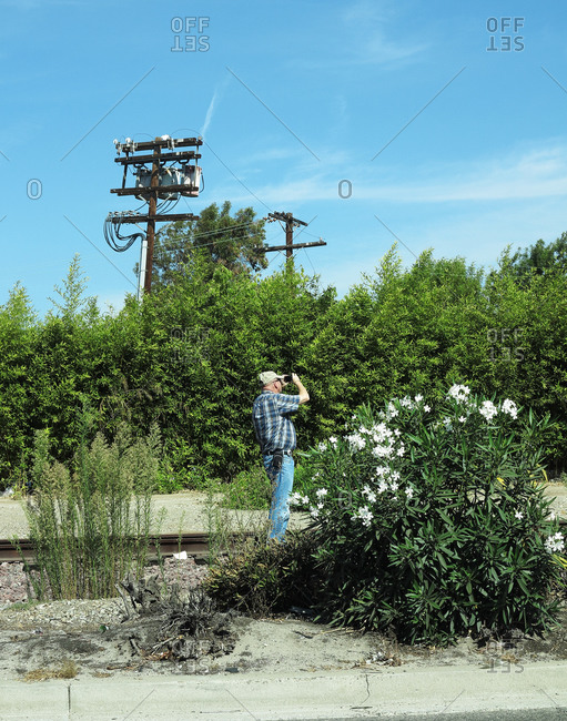Man taking a photograph at a railway track