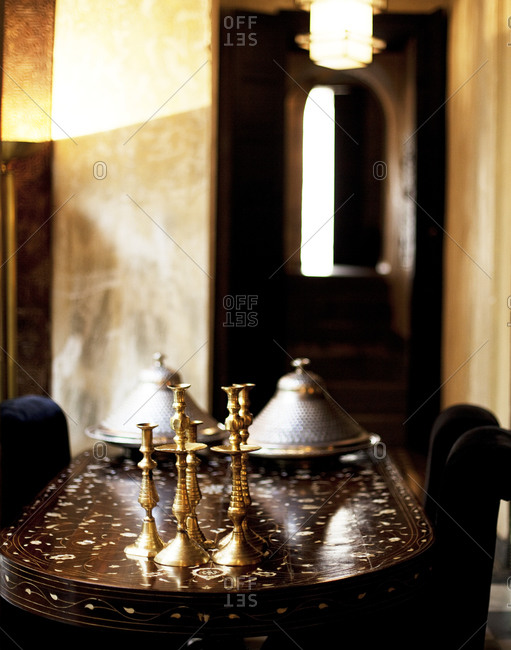 Golden candlesticks and silver containers on a table