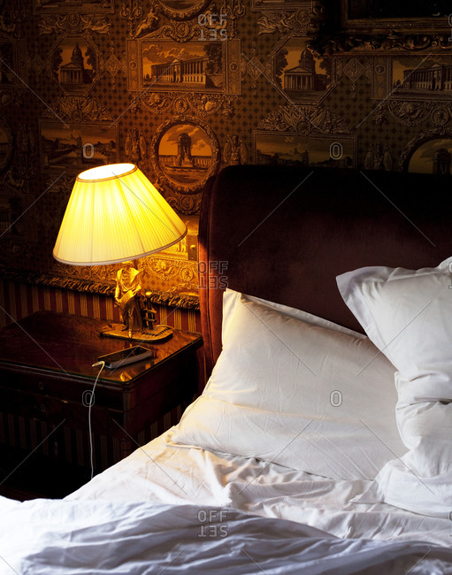 Close up of a bed with bedclothes and an antique lamp