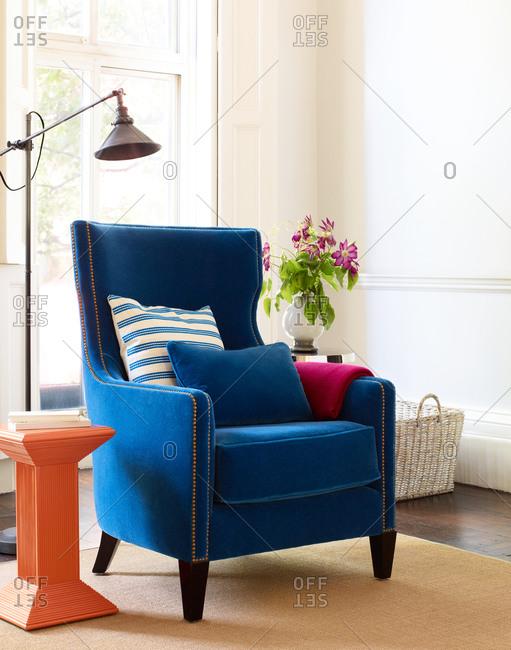 Blue velvet armchair and floor lamp