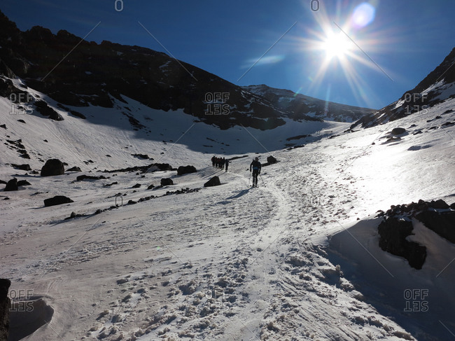 People hiking up a snowy mountain
