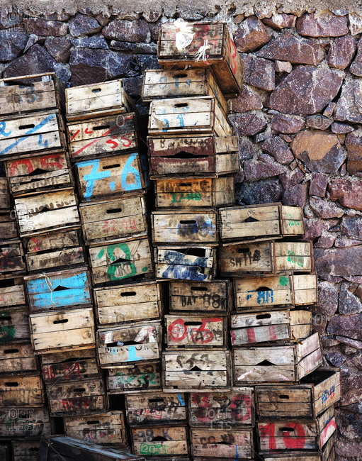 Wooden crates stacked by the stone wall