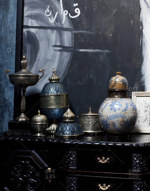 Antique porcelain pots and goblet on a chest of drawers