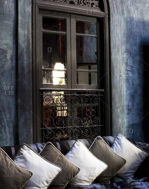 Divan with several pillows in front of a window