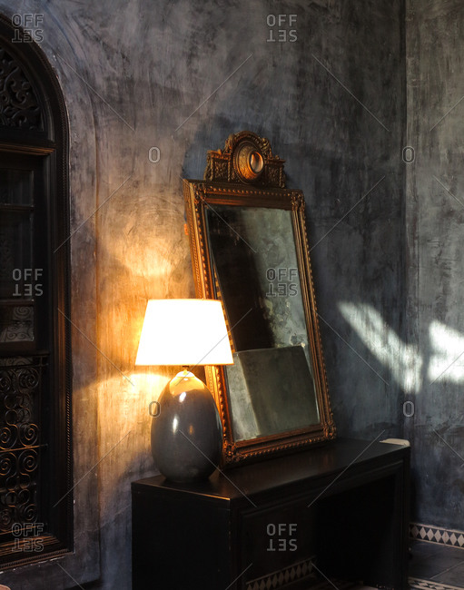 Chest of drawers with an antique mirror and lamp