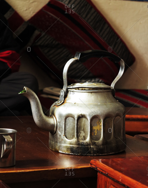 Dingy teakettle on wooden table