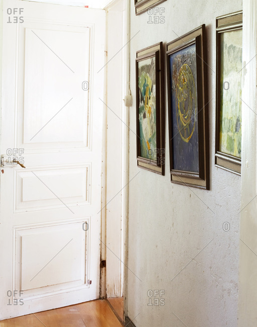 A hallway with painting hung on the wall