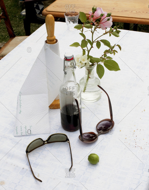 Sunglasses, paper towel and flowers on a table