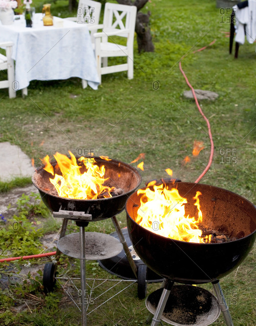 Two open grills with flames