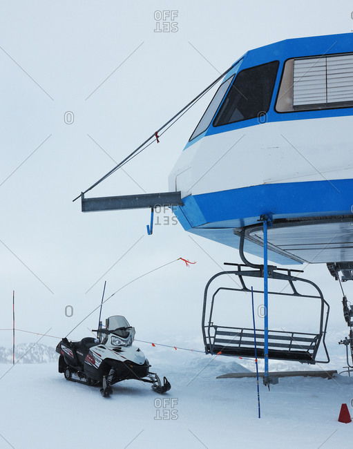 A snowmobile near a chairlift