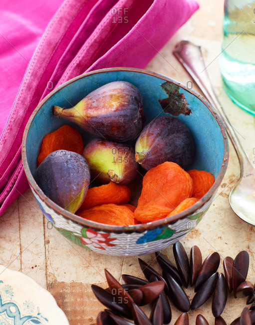 A bowl of whole figs and dried apricots