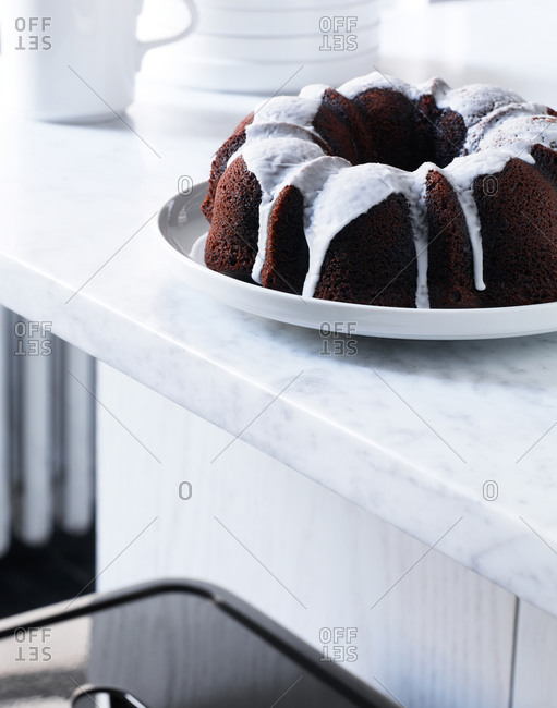 A chocolate bundt cake cooling off on a countertop