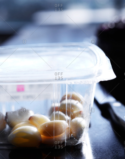 Whole garlic cloves in a plastic container