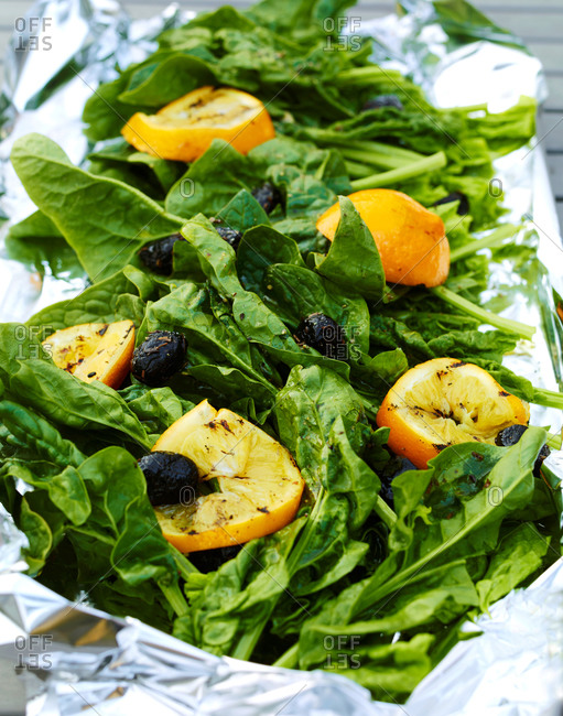 A spinach salad with olives