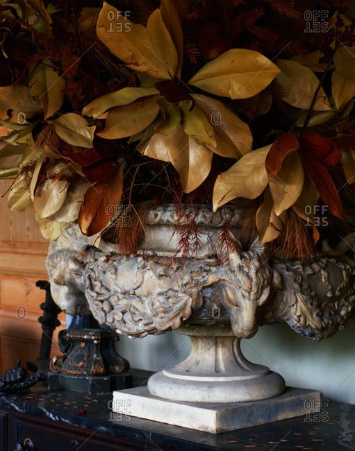 A large, stone vase full of decorative leaves