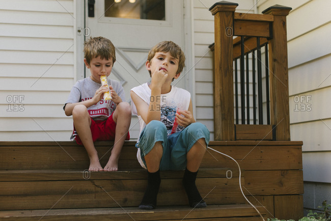 Two young boys sitting on the front porch eating ice pops
