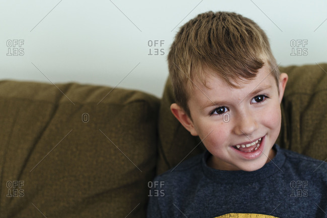 Boy sitting on a sofa laughing