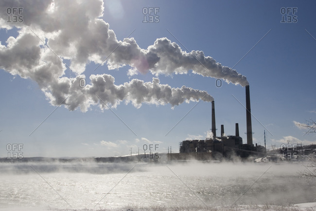 Coal fired power plant in winter with emissions blowing downwind