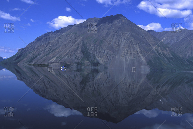 A mountain is reflected in a still lake.