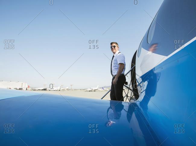Caucasian pilot leaving airplane on runway
