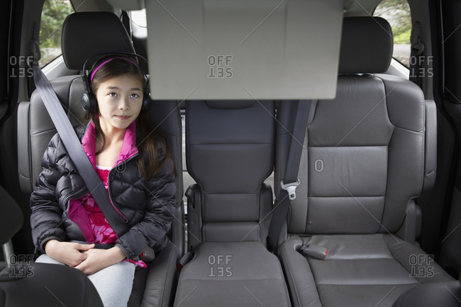 Mixed race girl watching television in backseat