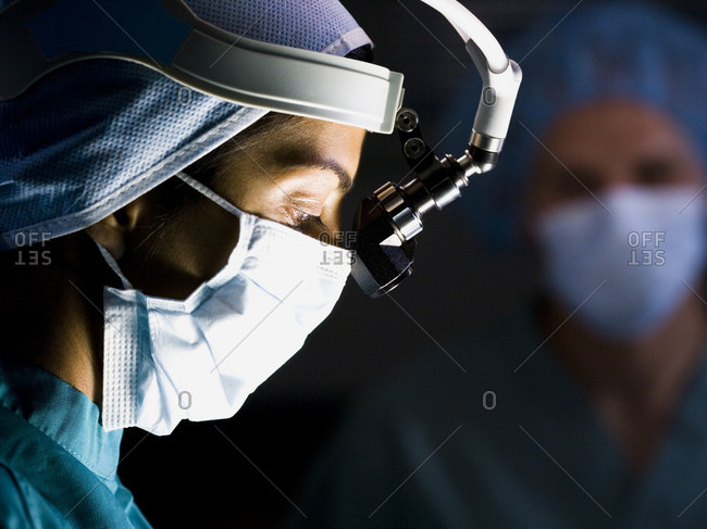 Male doctor in scrubs with head light in surgery