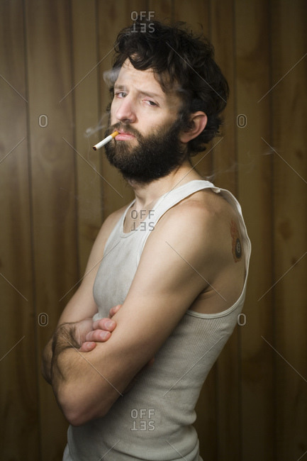 Man standing with cigarette and crossed arms