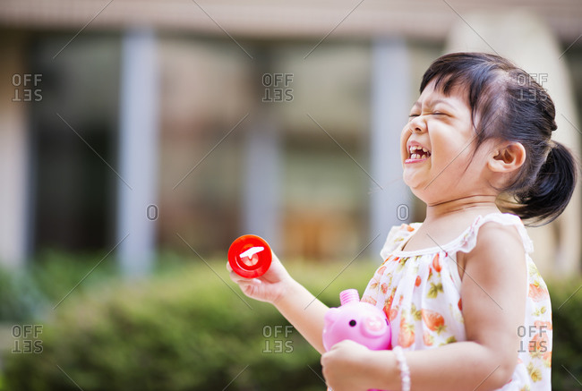Little girl laughing while holding bubble blowers